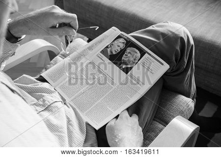 PARIS, FRANCE - NOV 2016: Man reading The Economist magazine with Donald Trump and Hillary Clinton after US President Election - Donald Trump is the 45th President of United States of America