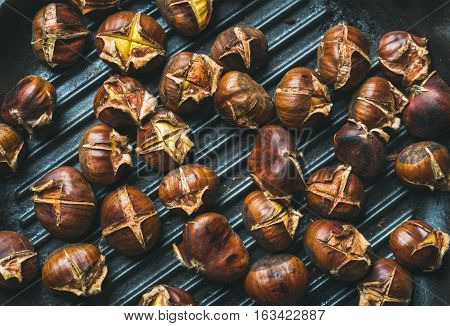 Close-up of roasted chestnuts over black cast iron grilling pan surface, top view, horizontal composition
