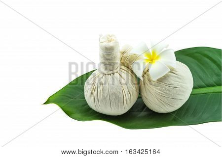 Spa herbal compressing ball and white frangipani flowers (Plumeria spp flower Apocynaceae flower Pagoda tree flower Temple tree flower) in green leaf isolate on white background.Saved with clipping path
