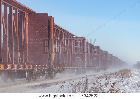 Line of empty brown flatcars blowing snow