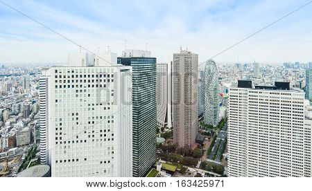 Business and culture concept - panoramic modern city skyline bird eye aerial view with mode gakuen cocoon tower under dramatic sun and morning blue cloudy sky in Tokyo Japan