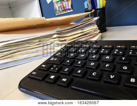 Buried in pile of paperwork in files on desk low angle view with keyboard and pens in office cubicle