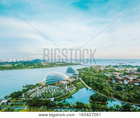 Business concept - panoramic modern city skyline bird eye aerial view of Gardens by the bay under dramatic morning blue cloudy sky in Singapore