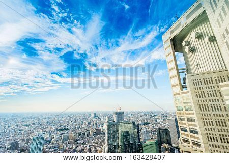 Business and culture concept - panoramic modern city skyline bird eye aerial view with Tokyo Metropolitan Government Building under dramatic sun and morning blue cloudy sky in Tokyo Japan