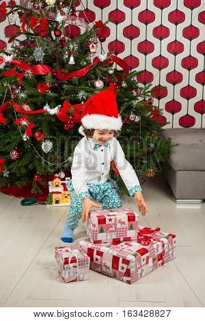 Happy little boy with Christmas gifts standing near tree