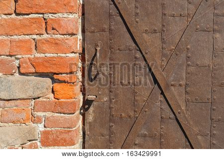 Detail of old iron door and brick wall closeup. Texture background