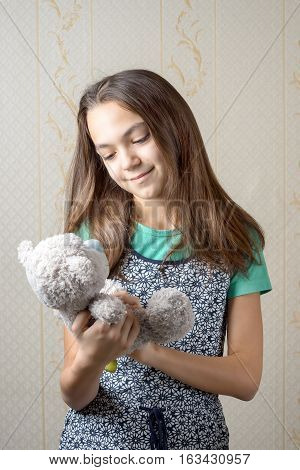 11 year old girl holding a teddy bear and looking at him with love