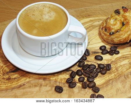 Latte coffee in a cup with coffee beans and a danish pastry on a wooden table