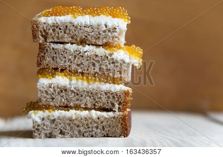 Multilayer sandwich of bread cream cheese and pike caviar close-up on light wood surface. Side view.