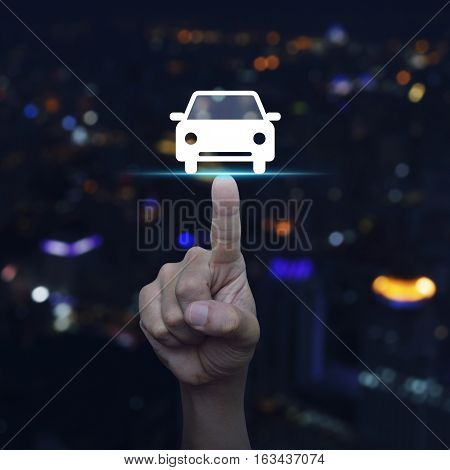Hand pressing car front view flat icon over blur colourful night light city tower Business service car concept