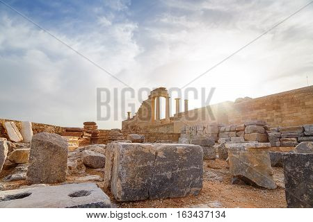 Greece. Rhodes. Acropolis of Lindos. Doric columns of the ancient Temple of Athena Lindia the IV century BC and the bay of St. Paul