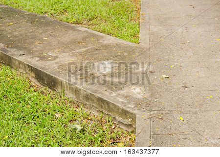 Junction of walking path or walkway or walkpath in garden with green grass.