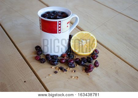 warm rose-hip tea red and white mug dried rosehips whole and crushed half a lemon and everything resting on a wooden table