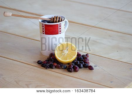 warm rose-hip tea with honey red and white mug dried rosehips whole and crushed half a lemon and everything resting on a wooden table