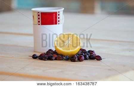 lemon and dried rosehips red and white mug dried rosehips whole and crushed and everything resting on a wooden table