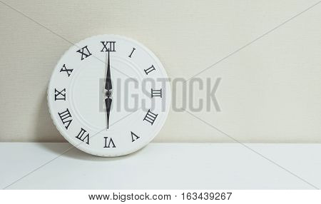 Closeup white clock for decoration at 6 o'clock on white wood desk and cream wallpaper textured background with copy space