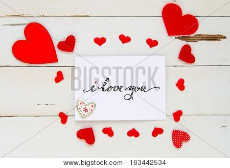 St Valentine's Day vintage overhead composition of hearts and hand drawn greeting note on wooden background