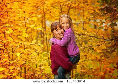 A woman holds her daughter in her arms and smile