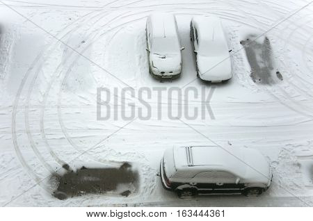 Ground parking cars after snowfall view from above. Automobiles covered with snow the traces of wheels. Empty space.