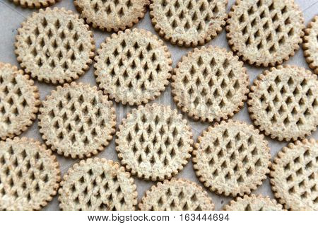 Food background. A lot round bran cookies laid out on a cardboard surface. Top view.