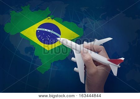 hand holding airplane with map of Brazil.