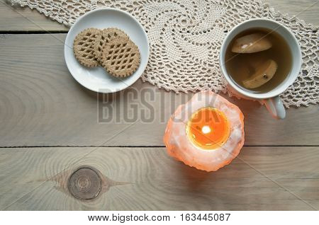 Cozy home still life. Candle of pink salt with fire a cup of apple compote and plate with cookies on knitted napkin on a light wooden background. Top view.