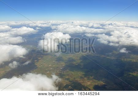 Sky scenery. Aerial view over the cumulus clouds and ground on a sunny day.