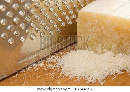 parmigiano con grattugia sul tavolo di legno