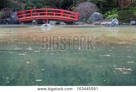 Sydney, Australia - May 22, 2016: At the popular Auburn Botanic Gardens, Japanese Zen Gardens section featuring the Ryoan-ji style designs. A traditional red arch bridge.