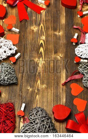 set of colorful decorative valentine hearts with checkered ribbon pegs or clothespins and cute bows in circle on brown vintage wooden background copy space