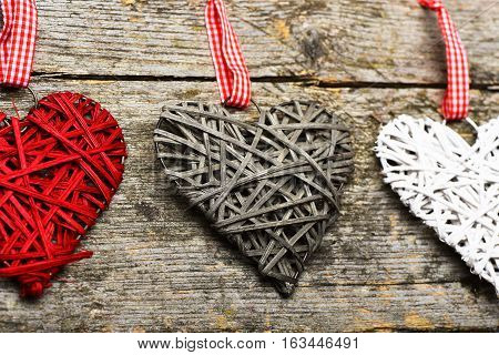 set of colorful decorative valentine hearts with checkered ribbon in line on old tacky vintage wooden background close up
