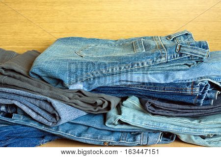 Many colored jeans on sale. Front view close-up