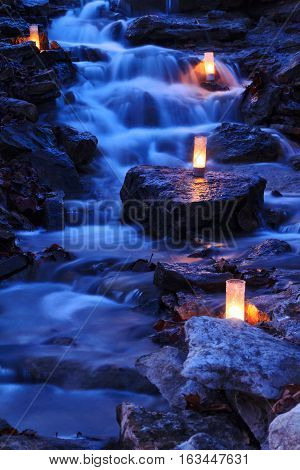 A cascading waterfall with candles during the twilight hours.