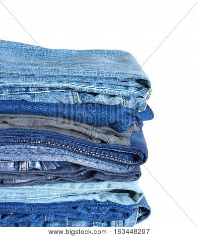 Stack on many colored jeans isolated on white background vertical view close-up