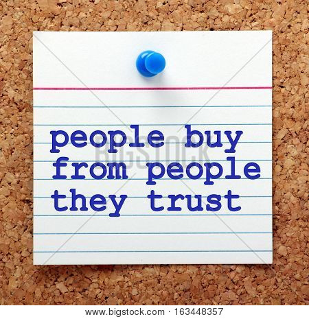 The words People Buy From People They Trust on a note card pinned to a cork notice board as a reminder that customer service and reliability results in brand loyalty