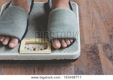 image of woman standing on weighing scale