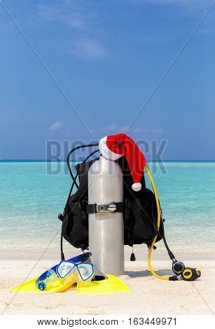 Scuba tank with Santa hat on tropical beach