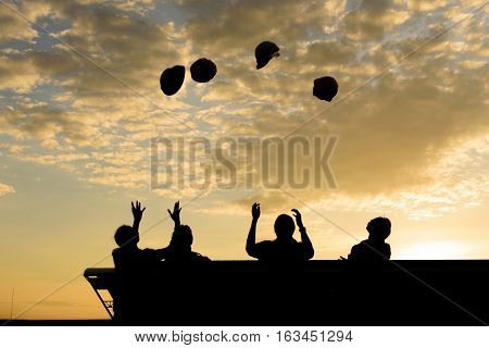 Silhouette of Engineers throwing up hat for celebrate after project successful in beautiful evening sky