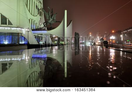 Grodno, Belarus - December 21, 2016: Night view of the city with illuminated street lights and reflection. Grodno Drama theater in the foreground.