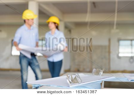 Several of construction design tools with Abstract blurred engineers reading blueprint and discuss about construction project