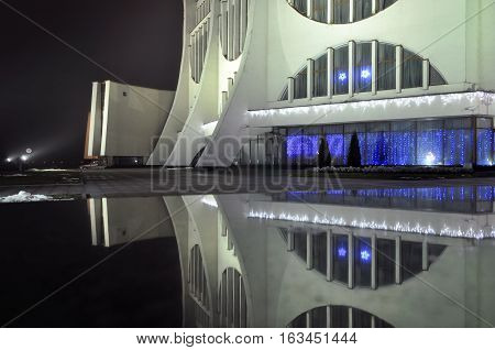 Grodno, Belarus - December 21, 2016: Glowing facade of Drama Theater in Grodno at night with reflection.