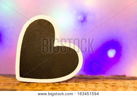 A black heart with white border in front of a colorful background