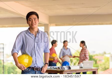 Asian male engineer standing in front of their meeting group