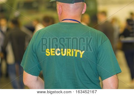 Man - security guard in uniform view from the back. People