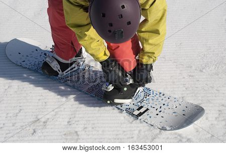 The athlete checks fastenings before descent from the mountain on a snowboard.