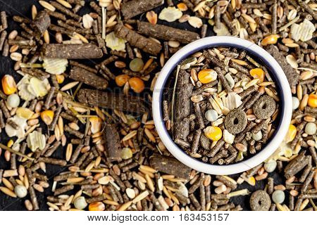 dry food for rodents in bowl on dark background top view.