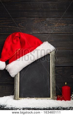 Red Santa hat on the chalkboard with snow and red candle. Frame with copyspace, Dreamlike Christmas background
