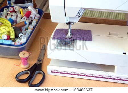 Electric sewing machine and sewing accessories: scissors, color spools with  thread and cloth closeup