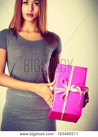 Occasions gifts people concept. Beautiful woman with pink gift. Young lady wearing nice gray outfit top and skirt holding present. Girl is mixed race