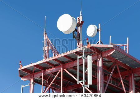 Telecommunications Tower With Many Antennas And Clear Blue Sky On Background